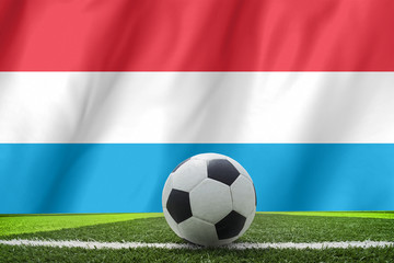 Soccer ball and national flag of Luxembourg lies on the green gr