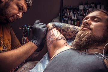 Tattoo artist doing tattoo in tatoo salon