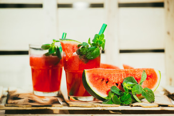 two watermelon smoothie and fresh on a light wood background. selective focus to mint