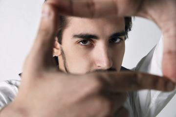 Closeup of young man framing photograph