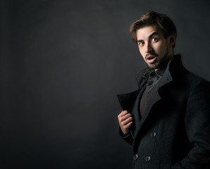 Young handsome man in coat on black background