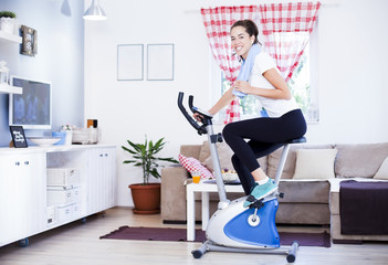 Sporty woman training on exercise bike using tablet in bright living room