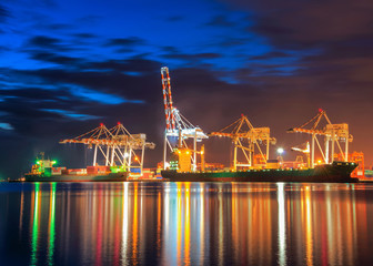 Wall Mural - Container Cargo freight ship with working crane bridge in shipyard at dusk.