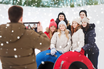group of smiling friends with snow tubes