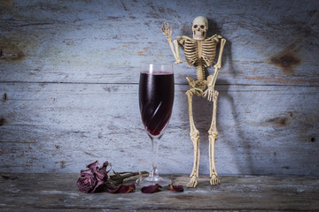 Still life Human Skeleton and wine on wooden background.