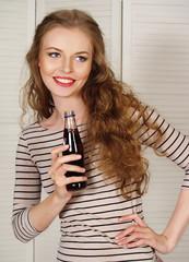 Cheerful girl in a striped shirt drinking soda