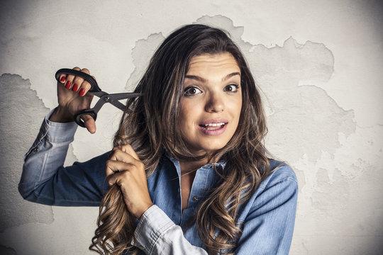 Beautiful girl cutting is own hair