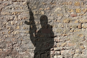 Shadow of man holding rifle