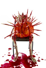bloody skeleton on the chair with horror thorn pumpkin