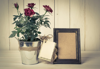 Retro photo frame and card with roses bouquet on wooden board