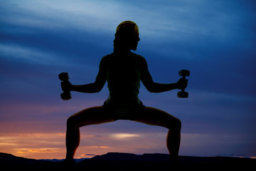silhouette woman doing squats weights out in blue sunset