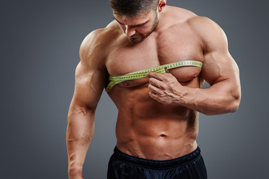 Closeup of muscular sports man measuring chest with tape measure isolated over gray background. Bodybuilder chest gain concept.