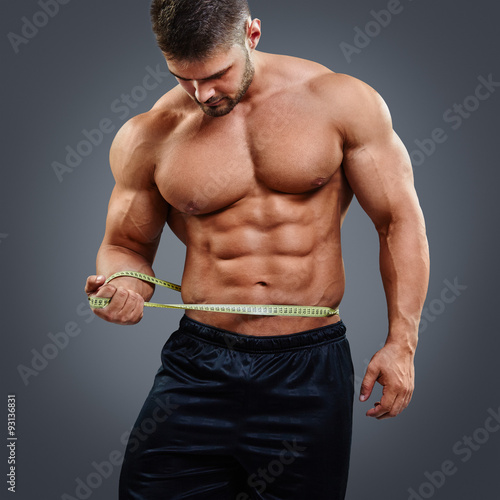 Muscular bodybuilder with six pack abs tries to measure his