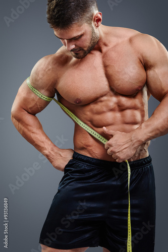 closeup handsome strong athlete measuring muscle biceps with tape measure isolated over gray. Black Bedroom Furniture Sets. Home Design Ideas