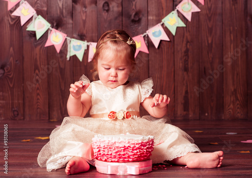 Cute baby girl eating birthday cake in room over wooden background