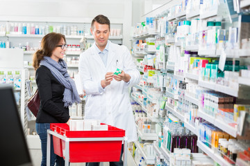 Pharmacist Showing Medicine To Female Customer In Pharmacy