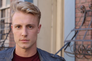close portrait of handsome adult blonde man, with blured urban classic background