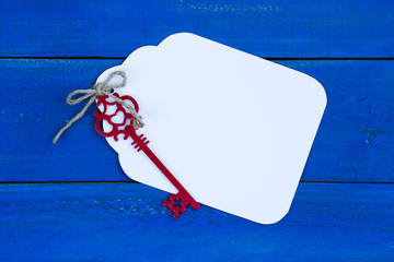 Blank white tag with key on royal blue wood background