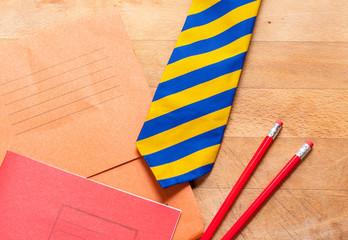 Schoolbooks, pencils and tie
