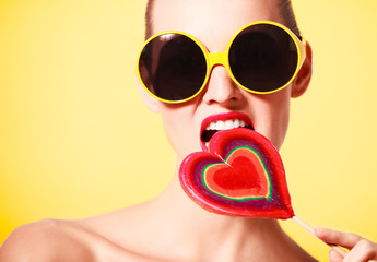 Woman with colorful heart shaped lollipop in sunglasses