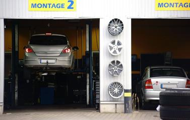 Autowerkstatt  / Eine Autowerkstatt mit zwei Garagen und zwei Autos auf Hebebühnen