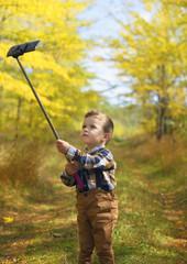 happy little boy taking selfie stick picture