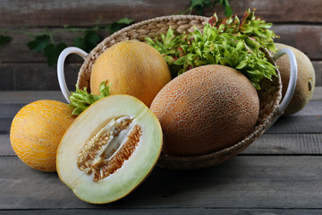 Ripe melons with green leaves in basket on table close up