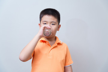 Asian boy drinking water from glass