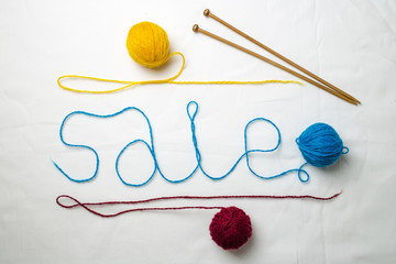 ord sale written multicolored yarn threads coiled into balls on a white background, near wooden spokes lie