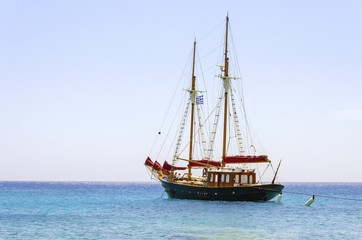 A traditional wooden sail boat anchored on the coast of Mykonos,Greece.Wind sails are down and it is tied on rocks by a rope.A very typical greek island summer holiday scene on crystal clear blue sea.