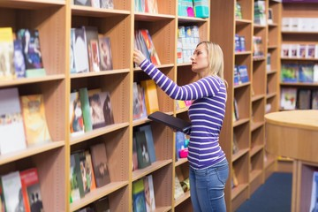 Young woman selecting book from bookshelf