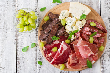 Printed roller blinds Appetizer Antipasto catering platter with bacon, jerky, sausage, blue cheese and grapes on a wooden background. Top view