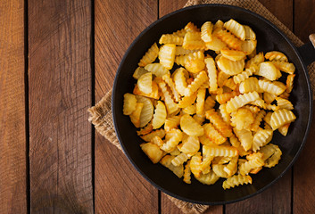 Frying pan with a fried potato in a rural way on a wooden background