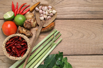 Thailand Food Ingredients: lemon, lime, galangal, ginger ,, tomato, mango leaves the dungeon, garlic on a wooden floor.