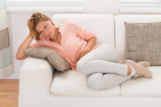 Woman On Sofa Having Stomachache
