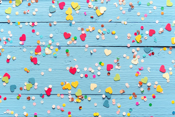 Blue wood background with scattered party confetti
