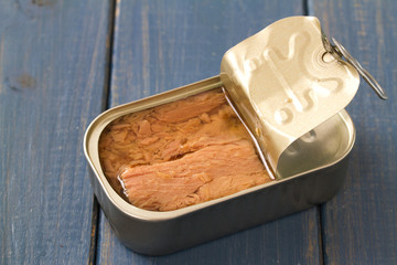 canned tuna on blue wooden background