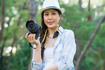 Beautiful asian girl smiling with digital camera photographing,