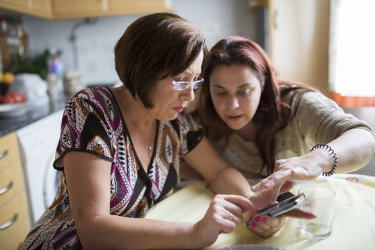 Woman helping senior woman how to use a smartphone