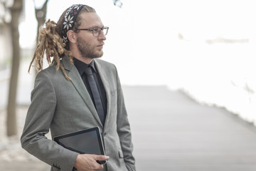 Portrait of a businessman with dreadlocks in suit holding digital tablet