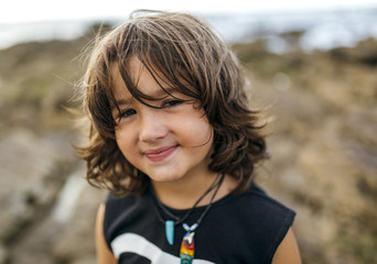 Spain, Gijon, portrait of smiling little boy with brown hair at rocky coast