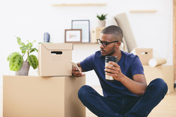 Young man sitting beside cardboard boxes having a coffee break