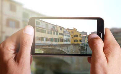 Male hand taking photo of Ponte Vecchio in Florence with cell, mobile phone.