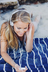 Smiling woman relaxing and listening music on the beach