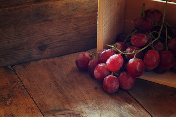 low key image of red grapes over wooden textured table