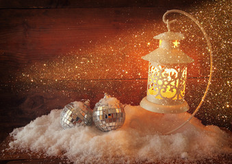 christmas background with white lantern, bauble and snow over wooden background