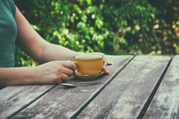 close up image of woman drinking coffee outdoors, next to wooden table at afternoon. filtered image. selective focus