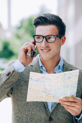 Young man on the phone holding map