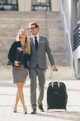 Happay businessman and businesswoman walking together with suitcase