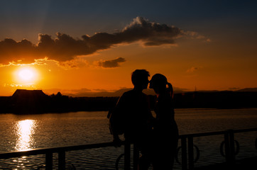Young couple silhouettes kissing at sunset